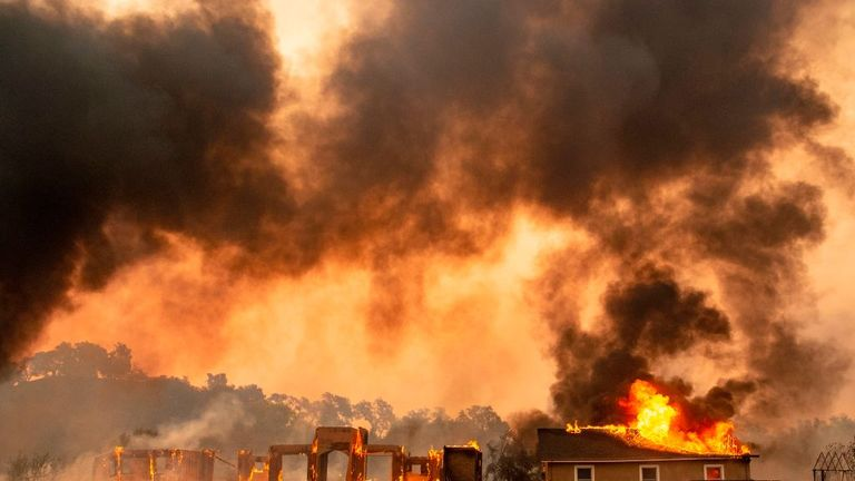 A building is engulfed in flames at a vineyard during the Kincade fire