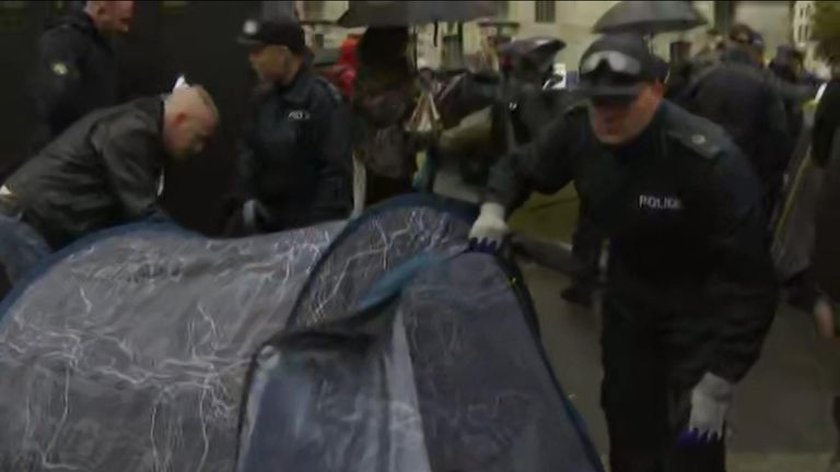 Officers talk to people in their tents