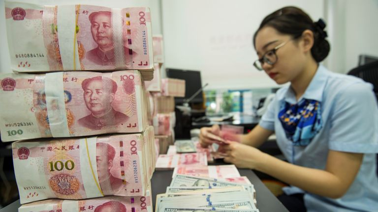 A Chinese bank employee counts 100-yuan notes and US dollar bills at a bank counter in Nantong in China's eastern Jiangsu province on August 28, 2019