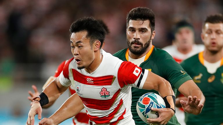 Japan's wing Kenki Fukuoka carries the ball past South Africa's centre Damian De Allende