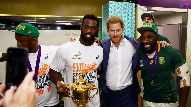 YOKOHAMA, JAPAN - NOVEMBER 02: In this handout image provided by World Rugby Prince Harry, Duke of Sussex (C) pose for a photo with Siya Kolisi of South Africa (L) holding the Web Ellis cup and Tendai Mtawarira of South Africa (R) after the Rugby World Cup 2019 Final between England and South Africa at International Stadium Yokohama on November 02, 2019 in Yokohama, Kanagawa, Japan. (Photo by Handout/World Rugby via Getty Images)