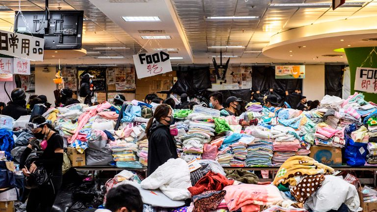 In this picture taken on November 14, 2019, protesters walk between aisles of goods donated by members of the public at the Hong Kong Polytechnic University in Hung Hom, Hong Kong. - Protests which began against a now-shelved extradition bill to China have spiralled into wider calls for democracy and police accountability as violence and demonstrations roil the city, challenging Beijing's authority. (Photo by Anthony WALLACE / AFP) (Photo by ANTHONY WALLACE/AFP via Getty Images)