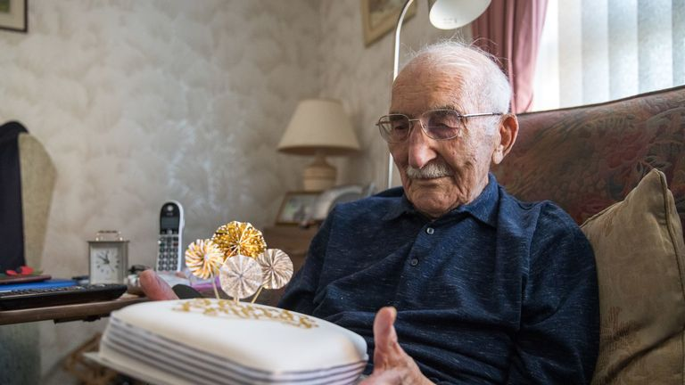 John Jenkins looks at a birthday cake, in his home, in Portsmouth, ahead of his 100th birthday. The D-Day veteran, who took part in a secret reconnaissance mission to check out the Normandy beaches for the Allied forces ahead of the June 1944 landings, is celebrating his 100th birthday.