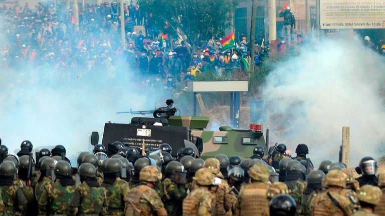"Bolivian riot police and soldiers clash with supporters of Bolivia's ex-President Evo Morales during a protest against the interim government in Sacaba, Chapare province, Cochabamba department  on November 15, 2019. - Bolivia's interim president Jeanine Anez said Friday that exiled ex-president Evo Morales would have to ""answer to justice"" over election irregularities and government corruption if he returns. (Photo by STR / AFP) (Photo by STR/AFP via Getty Images)"