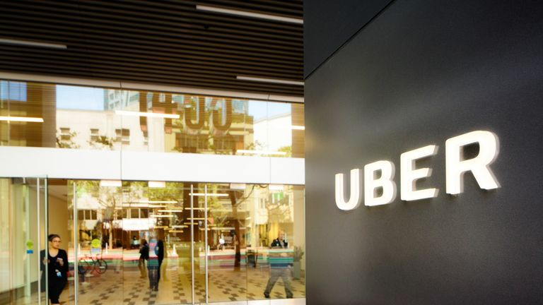 San Francisco, USA - May 12, 2016: Uber headquarters entrance in San Francisco with sign on the right. A woman is leaving the building through the front door. Reflections of Market street in the window.