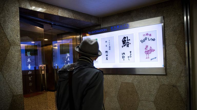 A man walks past the board of Sukiyabashi Jiro sushi restaurant (2nd R) in Tokyo on November 26, 2019. - The famed Tokyo sushi restaurant where Barack Obama is said to have enjoyed the best sushi of his life has been dropped from the latest Michelin gourmet guide after it stopped accepting reservations from the general public. (Photo by Behrouz MEHRI / AFP) (Photo by BEHROUZ MEHRI/AFP via Getty Images)