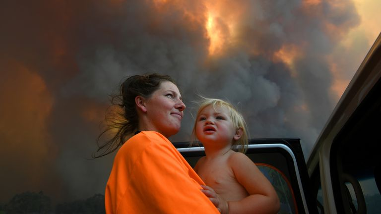 Sharnie Moren and her 18-month-old daughter Charlotte look on as thick smoke rises from bushfires near Nana Glen, Australia