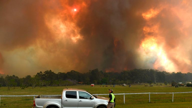 Locals watch as bushfires impact on farmland near the small town of Nana Glen