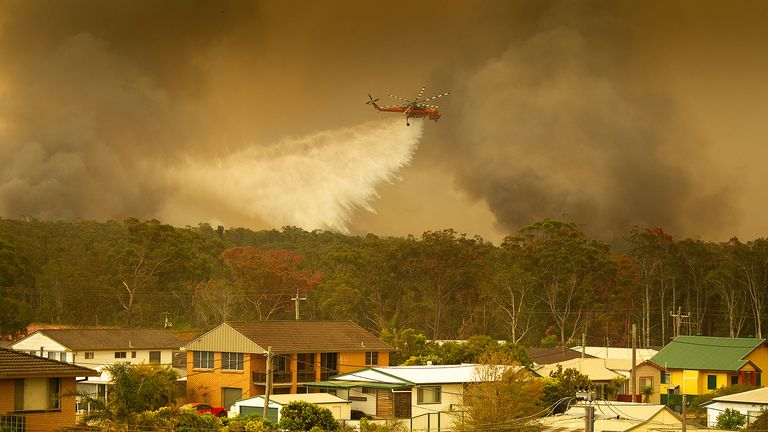 An helicopter drops water on a bushfire in Harrington, on the New South Wales coast
