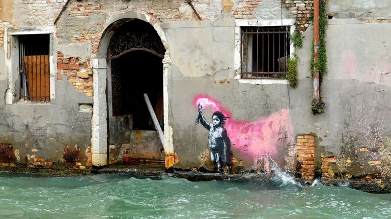 "The artwork by street artist Banksy, that portrays a migrant child wearing a lifejacket and holding a neon pink flare, is pictured after an exceptional overnight ""Alta Acqua"" high tide water level, on November 13, 2019 in Venice."