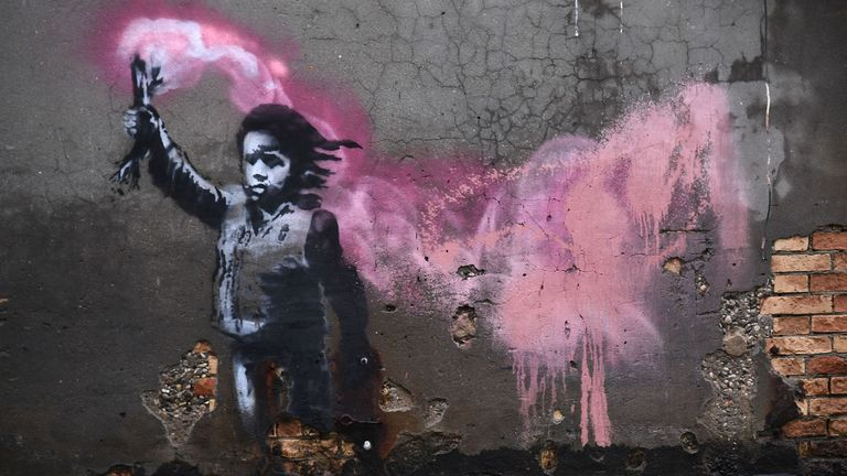 "The artwork by street artist Banksy, that portrays a migrant child wearing a lifejacket and holding a neon pink flare, is pictured after an exceptional overnight ""Alta Acqua"" high tide water level"