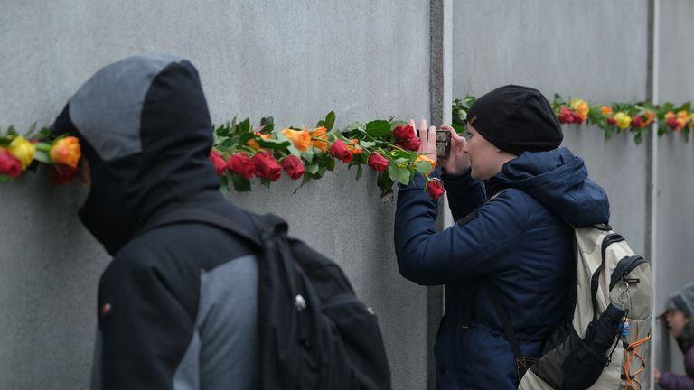 Roses were wedged into slats at a portion of the wall still standing