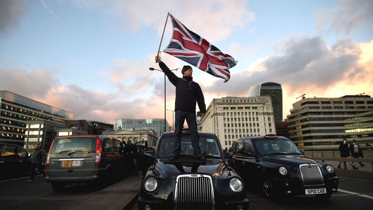 A black cab driver waves a Union Jack flag whilst standing on a taxi on London Bridge, during a protest against TfL and Uber