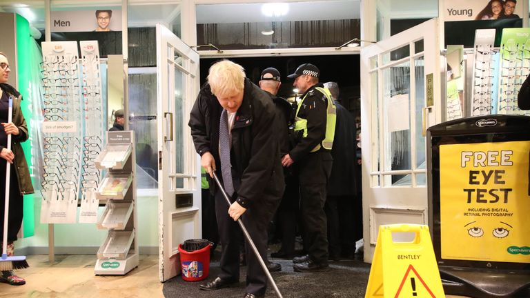 Boris Johnson helps with the clean up at a flooded opticians