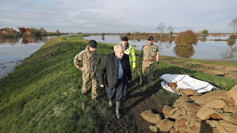 Boris Johnson walks with Lt Col Tom Robinson (left) from the Light Dragoons and an Environment Agency official  during a visit to Stainforth, Doncaster