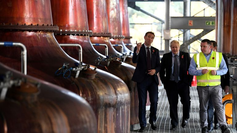 The prime minister walks through a whisky distillery in Scotland