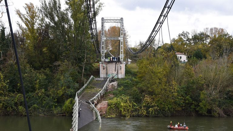 Rescuers attend the scene of a suspension bridge collapse near Toulouse