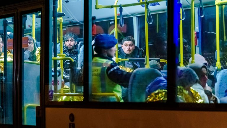 A bus with refugees drives away from the ferry in the harbour of Vlaardingen
