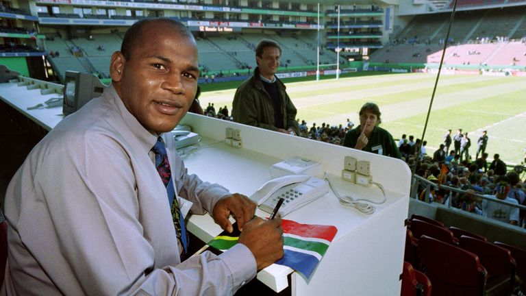 Then injured South African winger Chester Williams signs an autograph on a South African flag in the press box at Newlands on May 25, 1995, before the opening match of the rugby World Cup in Cape Town. - Chester Williams, the left winger in South Africa's side that won the 1995 Rugby World Cup, died on September 6, 2019 aged 49, a relative told AFP