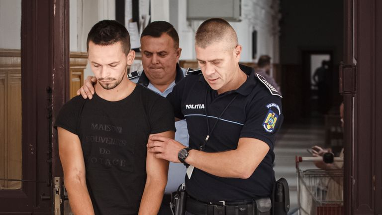Cristian Sabou is escorted by an officer after a hearing to confirm his European Arrest Warrant