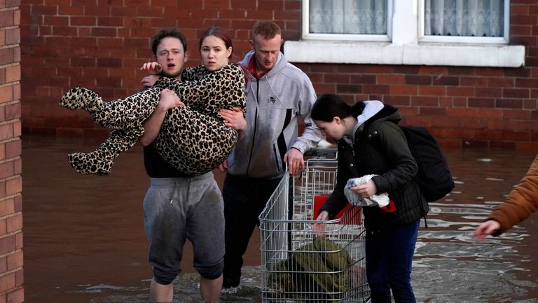 A woman is carried by a man as he wades through floodwater in Doncaster