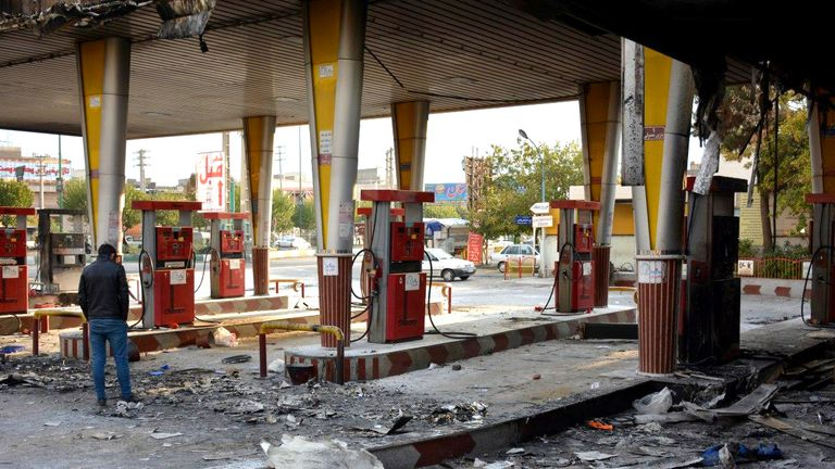 An Iranian man checks a scorched gas station that was set ablaze by protesters during a demonstration against a rise in gasoline prices in Eslamshahr, near the Iranian capital of Tehran, on November 17, 2019