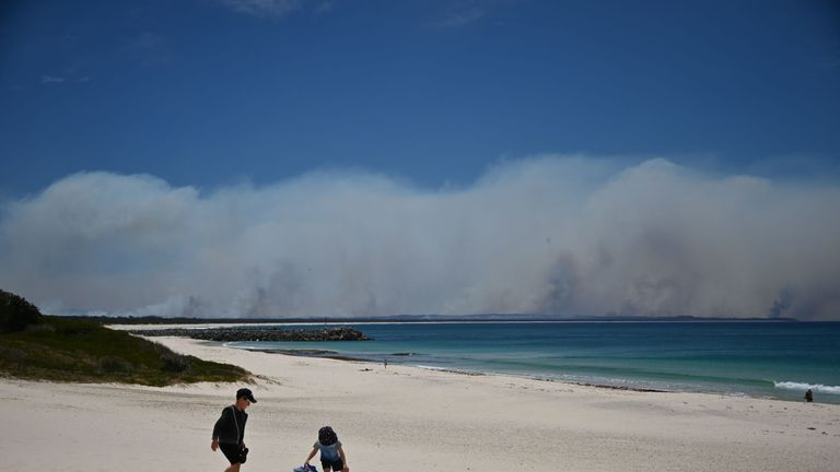 Bushfires burn in the distance as children play on a beach in Forster, 300km north of Sydney on November 9, 2019, as firefighters try to contain dozens of out-of-control blazes that are raging in the state of New South Wales