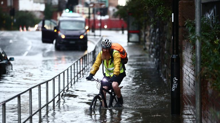 A man attempts to cycles through a flooded street in Sheffield