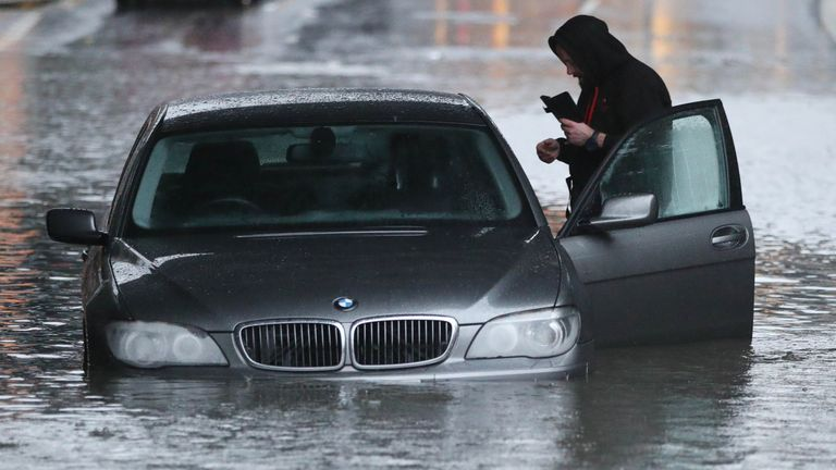 A man with car in a flooded street Sheffield on Thursday