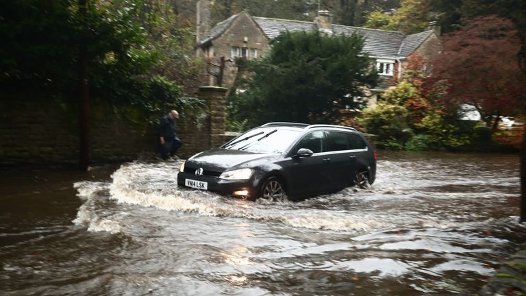 A car passing through a flooded road in Whirlow, Sheffield