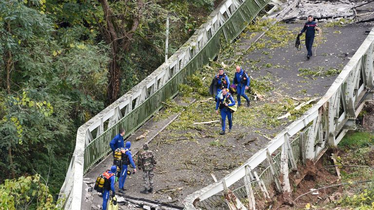 Rescuers walk on a suspension bridge which collapsed on Monday morning