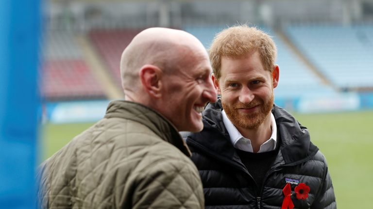 Prince Harry, Duke of Sussex, looks at former rugby player Gareth Thomas at the Twickenham Stoop in London