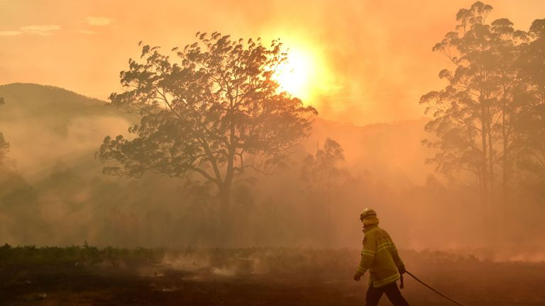 A firefighter defends a property from a bushfire at Hillville near Taree, 350km north of Sydney on November 12, 2019
