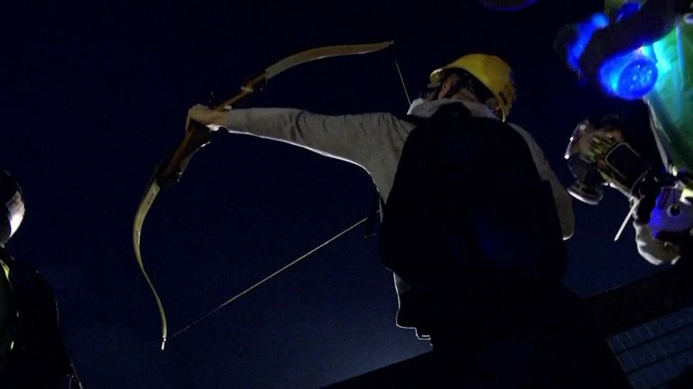 A protester used a bow and arrow to fight back against police as clashes in Hong Kong carried into the night
