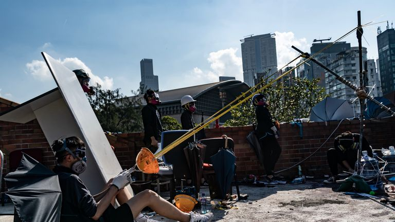 Protesters use a catapult to fire a brick at the Hong Kong Polytechnic University