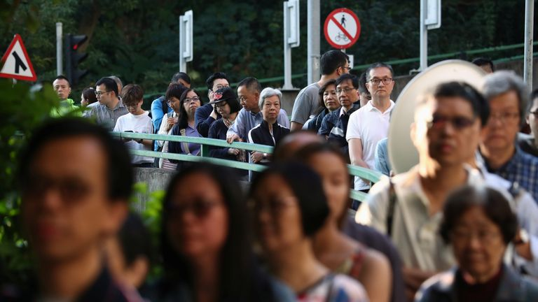 Voters line up at a polling station during district council local elections in Hong Kong