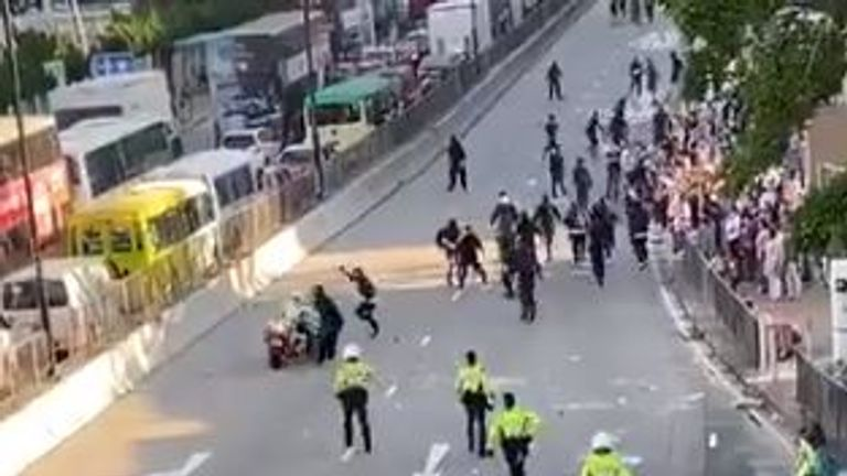 A policeman appears to deliberately run into a group of protesters. Pic: Twitter/Joshua Wong