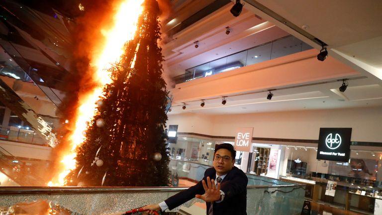 A man tries to extinguish a burning Christmas tree at Festival Walk mall in Kowloon Tong, Hong Kong