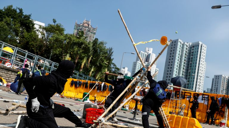 Student protesters use a giant improvised slingshot to fling tennis balls across a barricade