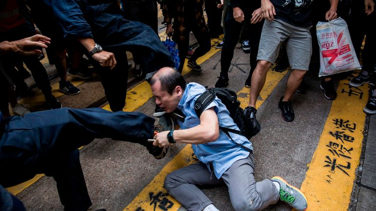 A man is beaten after getting in an argument during a demonstration of office workers and protesters