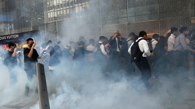 People react after police fire tear gas during a demonstration