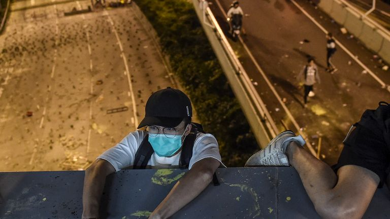 Protesters lower themselves with a rope down from a bridge to a highway, to escape from Hong Kong Polytechnic University campus and from police, in Hung Hom district in Hong Kong on November 18, 2019. - Dozens of Hong Kong protesters escaped a besieged university campus on November 18 by lowering themselves on a rope from a footbridge to a highway, AFP video showed. Once on the road they were seen being picked up by waiting motorcyclists. (Photo by Ye Aung THU / AFP) (Photo by YE AUNG THU/AFP vi