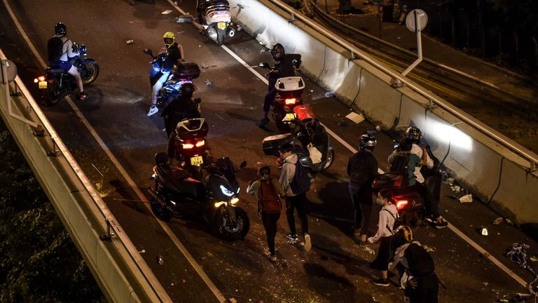 Protesters get a lift from motorbikes waiting on a highway