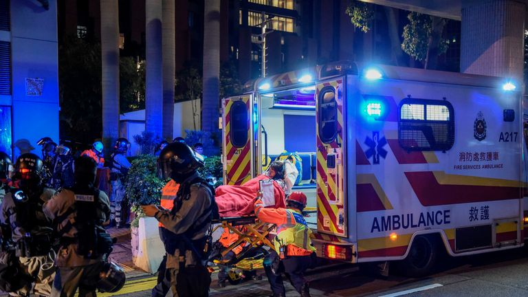 A student is lifted onto an ambulance after she fell down while attempting to lower herself