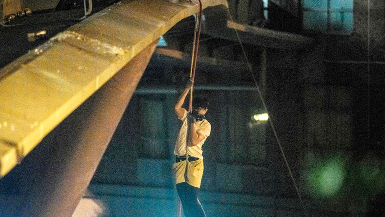 A protester lowers himself down a rope from a bridge to a highway, to escape from Hong Kong Polytechnic University campus