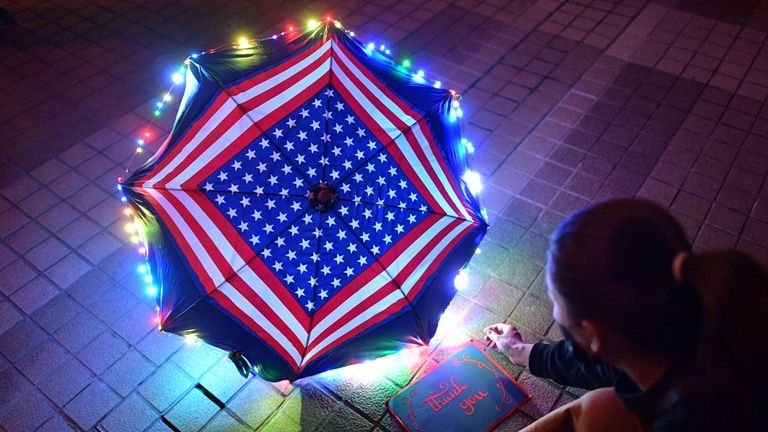 A pro-democracy protester sits beside a thank you note and an umbrella bearing patterns of the US national flag