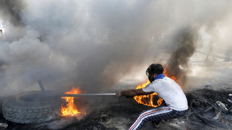 An Iraqi demonstrator pulls a burning tire during ongoing anti-government protests