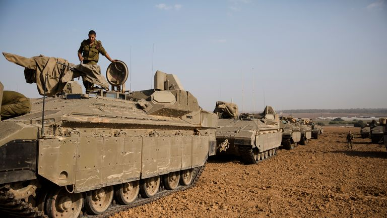 An Israeli soldier stands on top an armoured personnel carrier