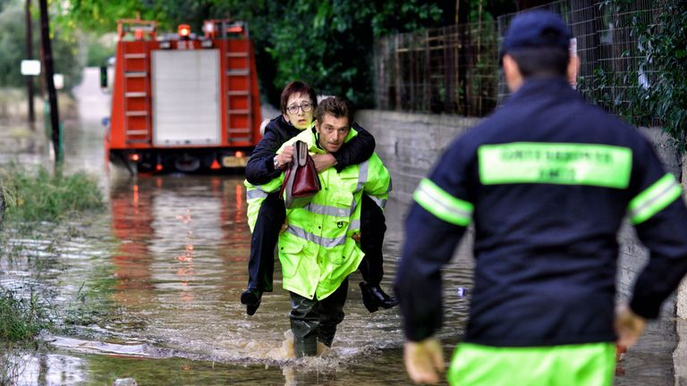 A woman is rescued in from a flooded street in the Greek town of Kineta