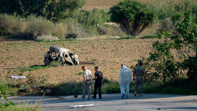 Police and forensic experts inspect the wreckage of a car bomb believed to have killed the investigative journalist